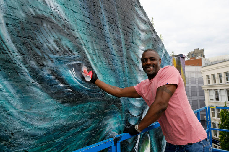 "Idris Elba paints in the eye of his character ""Krall"" during the unveiling of a Star Trek Beyond mural by artist Jim Vision in Clerkenwell, London."