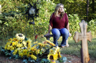 Heather Melton sits by the grave of her husband, Sonny, on the grounds of their home in Tennessee