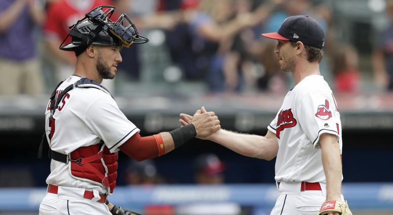 Cleveland Indians' Yan Gomes, left, and relief pitcher Josh Tomlin celebrate after the Indians defeated the Chicago White Sox 12-0 in a baseball game, Wednesday, June 20, 2018, in Cleveland.