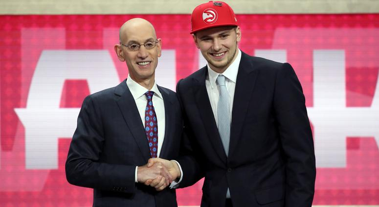 Luka Doncic, who plays for Real Madrid, poses for a picture with NBA Commissioner Adam Silver after Doncic was picked third overall by the Atlanta Hawks during the NBA basketball draft in New York, Thursday, June 21, 2018.