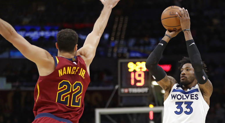Minnesota Timberwolves' Robert Covington (33) shoots against Cleveland Cavaliers' Larry Nance Jr. (22) in the second half of an NBA basketball game, Monday, Nov. 26, 2018, in Cleveland. (AP Photo/Tony Dejak)