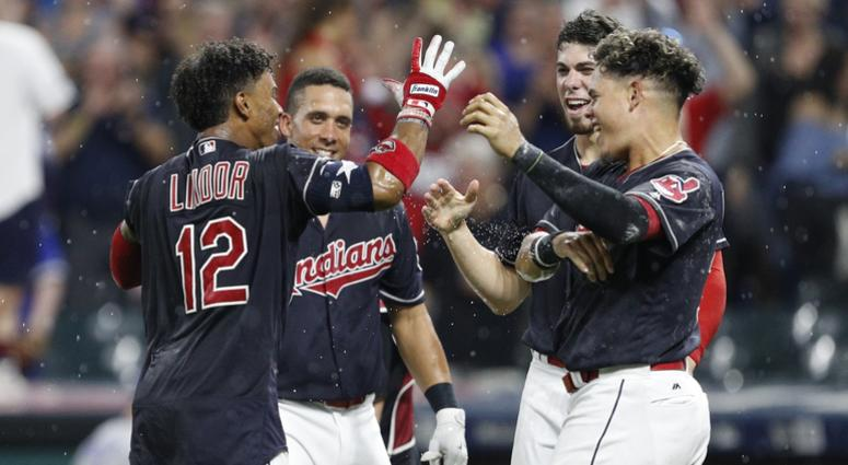 Jul 22, 2017; Cleveland, OH, USA; Cleveland Indians shortstop Francisco Lindor (12) celebrates with left fielder Michael Brantley (23) and center fielder Bradley Zimmer (4) and third baseman Giovanny Urshela (right) after hitting a walk off home run durin
