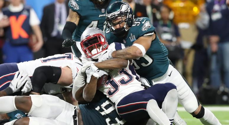 New England Patriots running back Dion Lewis (33) runs with the ball against Philadelphia Eagles linebacker Mychal Kendricks (95) and tackle Tim Jernigan (93) in Super Bowl LII