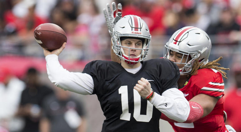 Apr 14, 2018; Columbus, OH, USA;Gray Team quarterback Joe Burrow (10) sends a pass upfield under pressure from Scarlet Team defensive end Chase Young (2) during the Spring Game at Ohio Stadium.