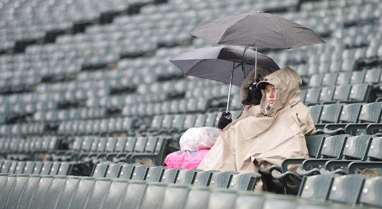 Apr 14, 2018; Cleveland, OH, USA; Fans wait in the rain as the game between the Cleveland Indians and the Toronto Blue Jays is delayed at Progressive Field.