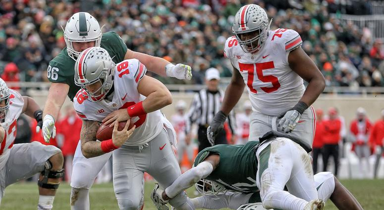 Ohio State Buckeyes quarterback Tate Martell (18) is tripped up by Michigan State Spartans cornerback Justin Layne (2) during the first half of a game at Spartan Stadium.