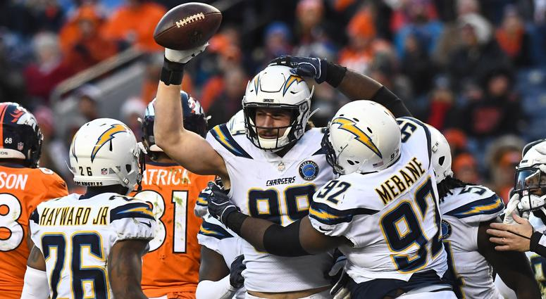 Los Angeles Chargers defensive end Joey Bosa (99) reacts with cornerback Casey Hayward Jr. (26) and nose tackle Brandon Mebane (92) after a fumble recovery in the third quarter against the Denver Broncos at Broncos Stadium at Mile High.