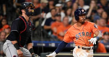 Houston Astros' Tony Kemp watches his two-run double in front of Cleveland Indians catcher Yan Gomes during the seventh inning of a baseball game Friday, May 18, 2018, in Houston.