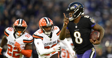 Baltimore Ravens quarterback Lamar Jackson, right, rushes for a touchdown past Cleveland Browns free safety Jabrill Peppers, back left, and strong safety Damarious Randall in the first half of an NFL football game, Sunday, Dec. 30, 2018, in Baltimore. (AP