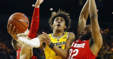 Michigan guard Jordan Poole (2) scores between Ohio State forward Justin Ahrens, left, and guard Keyshawn Woods during the second half of an NCAA college basketball game Tuesday, Jan. 29, 2019, in Ann Arbor, Mich. (AP Photo/Carlos Osorio)