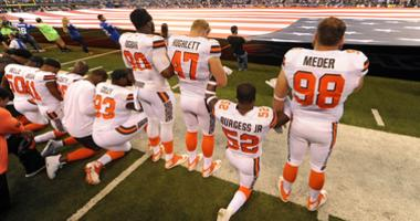 The Cleveland Browns team stand and kneel during the National Anthem before the start of their game against the Indianapolis Colts at Lucas Oil Stadium.