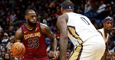 Cleveland Cavaliers forward LeBron James (23) is defended by New Orleans Pelicans forward DeMarcus Cousins (0) during the first half of a game at the Smoothie King Center.