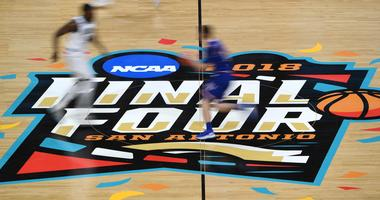 Kansas Jayhawks and Villanova Wildcats cross the center court logo in the first half in the semifinals of the 2018 men's Final Four at Alamodome.