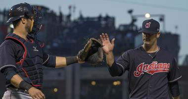 Cleveland Indians starting pitcher Adam Plutko (right) celebrates with catcher Yan Gomes (left) after the third inning against the Chicago Cubs at Wrigley Field
