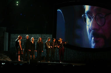 A photo of the late Warren Zevon overlooks his friends performing