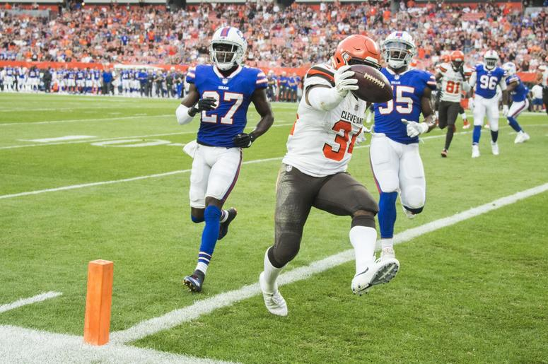 Cleveland Browns running back Carlos Hyde (34) scores a touchdown as Buffalo Bills cornerback Tre'Davious White (27) and defensive end Jerry Hughes (55) pursue during the first quarter at FirstEnergy Stadium.