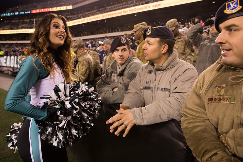 A Philadelphia Eagles cheerleader talks with members of the military during the fourth quarter against the Dallas Cowboys at Lincoln Financial Field.