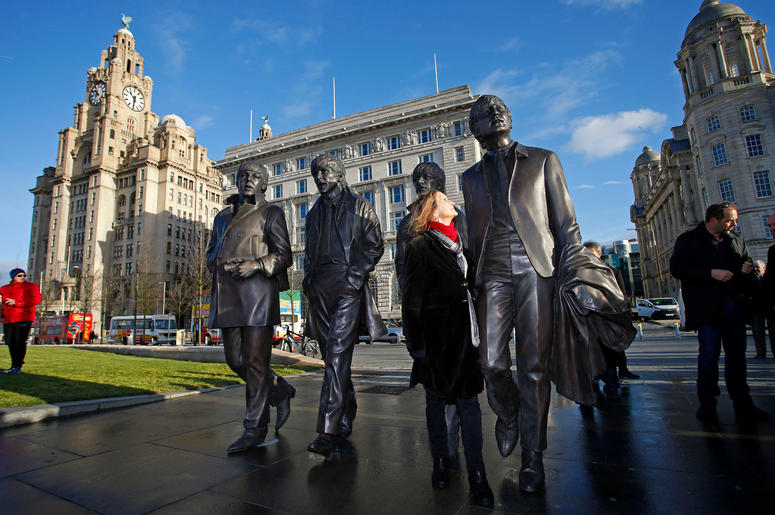 A new statue of the Beatles is unveiled by John Lennon's sister Julia Baird (centre) outside the Liverbuilding, in Liverpool.