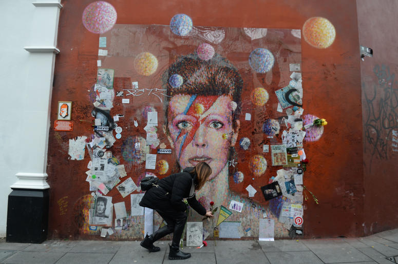 A woman lays a rose at a mural of David Bowie in Brixton, London on the second anniversary of his death.