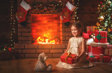 Happy child girl with christmas gift at home
