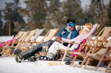 Winter holiday, ski, travel - couple relaxing together in sun at