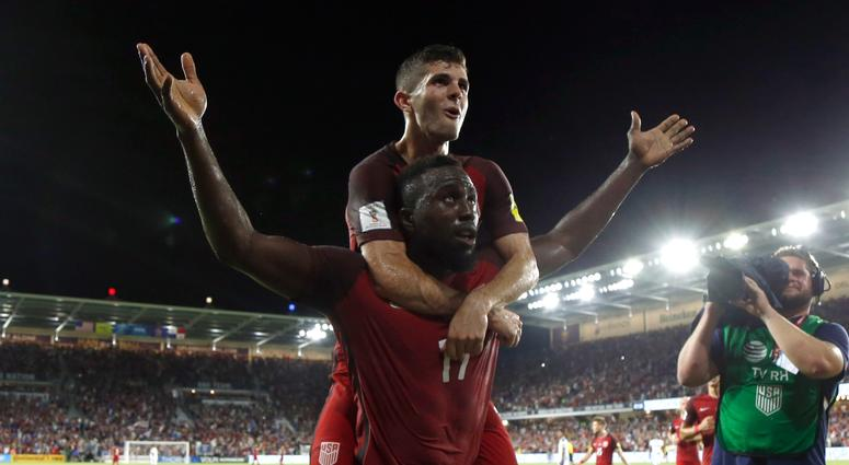 Christian Pulisic jumps on the back of USA soccer teammate Jozy Altidore.
