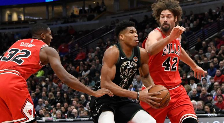 Bucks forward Giannis Antetokounmpo (34) drives the ball while defended by Bulls center Robin Lopez (42) and guard Kris Dunn (32).