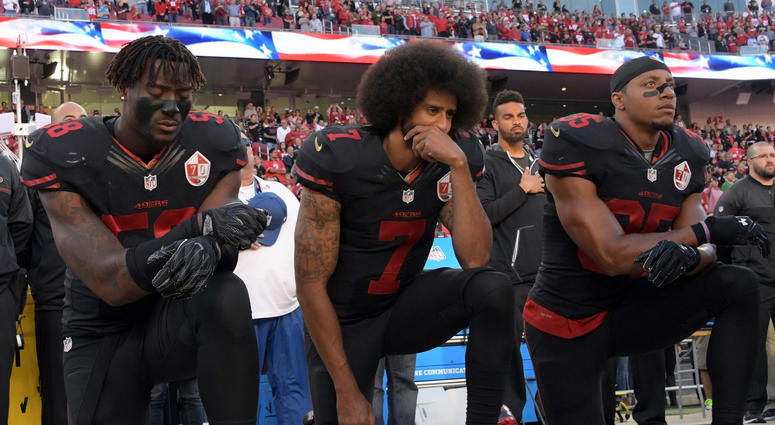 49ers outside linebacker Eli Harold (58), quarterback Colin Kaepernick (7) and safety Eric Reid (35) kneel in protest during the national anthem before a game in 2016.