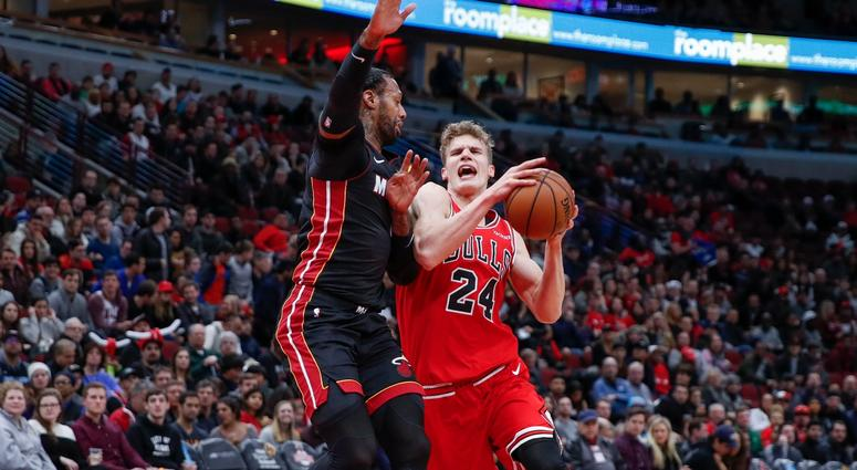 Bulls forward Lauri Markkanen (24) is fouled by Heat forward James Johnson (16).