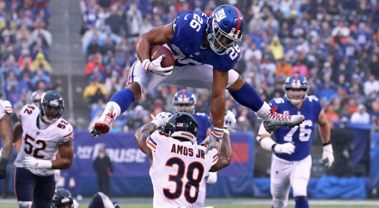 Giants running back Saquon Barkley leaps over Bears safety Adrian Amos for extra yards.
