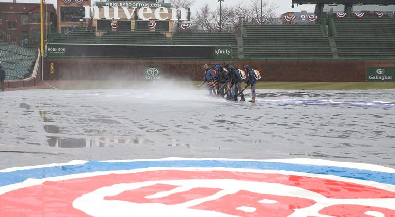 The grounds crew at Wrigley Field cleans the tarp off.
