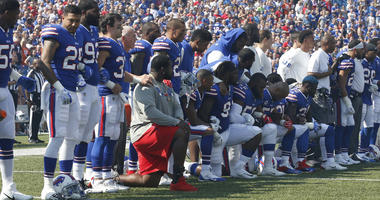 Bills players kneel in protest during the national anthem before a game.