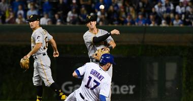Pirates shortstop Kevin Newman (27) throws to first base after forcing Cubs third baseman Kris Bryant (17) out at second.