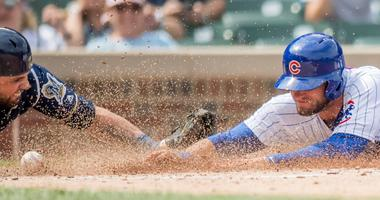 Cubs third baseman David Bote (13) slides into home plate to score as Brewers catcher Manny Pina looks to apply the tag.