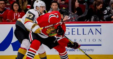 Blackhawks center David Kampf (64) controls the puck against Golden Knights defenseman Shea Theodore (27).