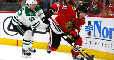 Blackhawks center Drake Caggiula (91) controls the puck in front of Stars defenseman Taylor Fedun (42).