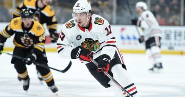 Blackhawks center Dylan Strome (17) skates with the puck.