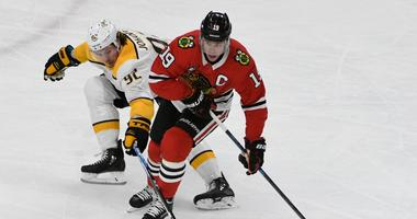 Blackhawks center Jonathan Toews (19) and Predators center Ryan Johansen (92) battle the puck.