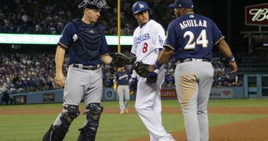 Brewers first baseman Jesus Aguilar (24) takes issues with Dodgers shortstop Manny Machado (8) after Machado clipped Aguilar's foot on a play at first base.