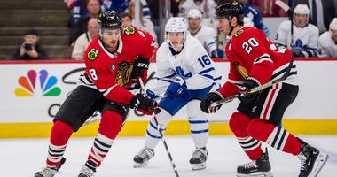 Blackhawks center Nick Schmaltz (8) controls the puck against the Maple Leafs.