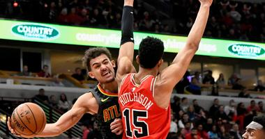 Hawks guard Trae Young (11) passes the ball around Bulls forward Chandler Hutchison (15).