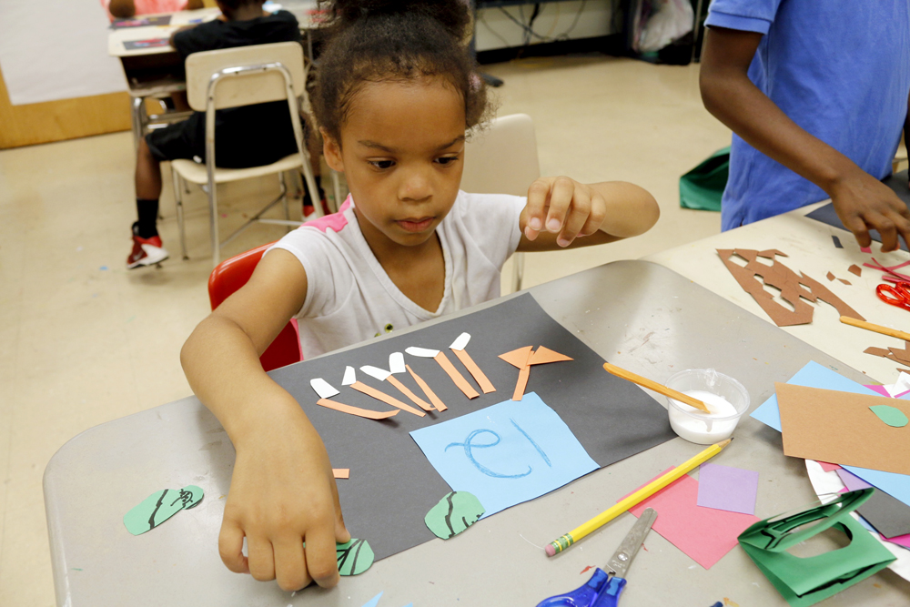 Young Audiences Summer Arts Academy First grader creating Math Monsters with cut paper