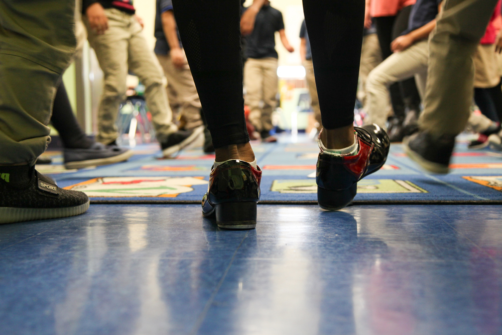 The heel of Quynn's red and black tap shoes strikes the floor in the foreground. In the background, kindergardeners' tennis shoes imitate the dance step.