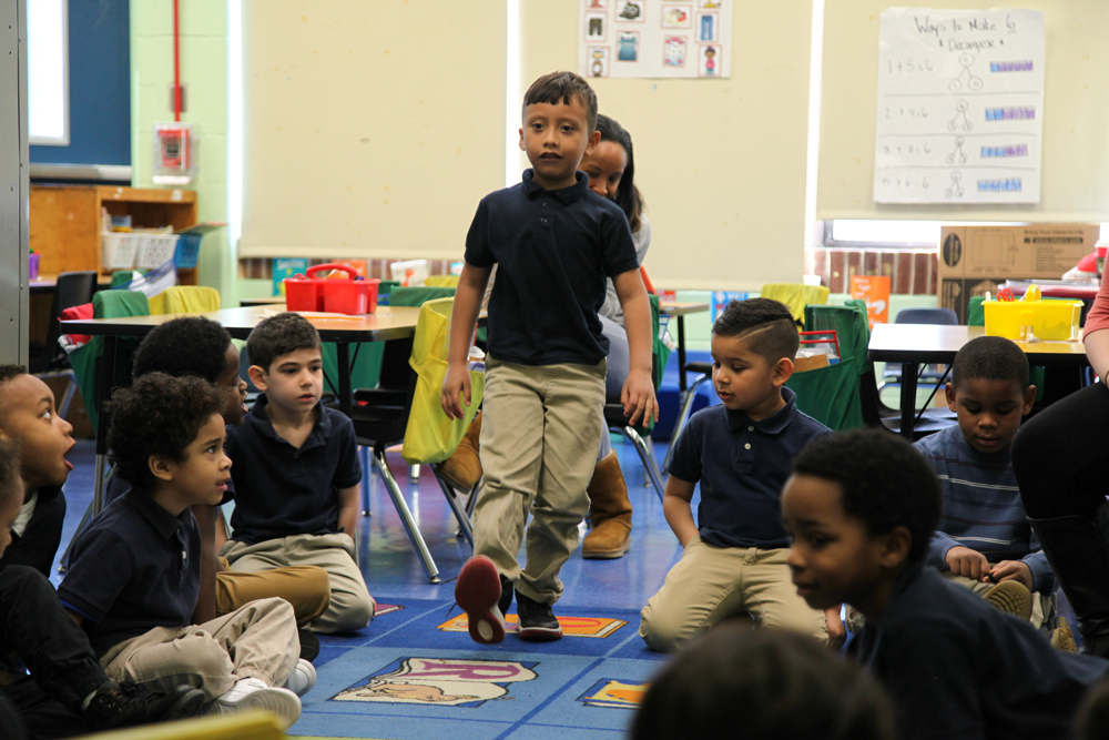 "A kindergarten student models a ""heel-toe"" tap movement by striking the heel of his sneaker to the floor. His classmates sit in a circle on the rug and watch carefully."