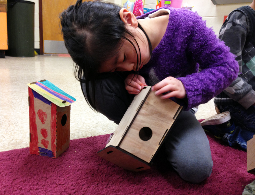 A child assembling a laser-cut, wooden birdhouse