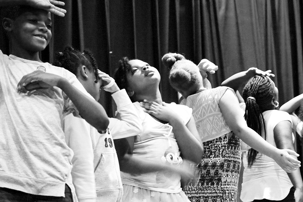 Children on stage in a row striking a very dramatic pose