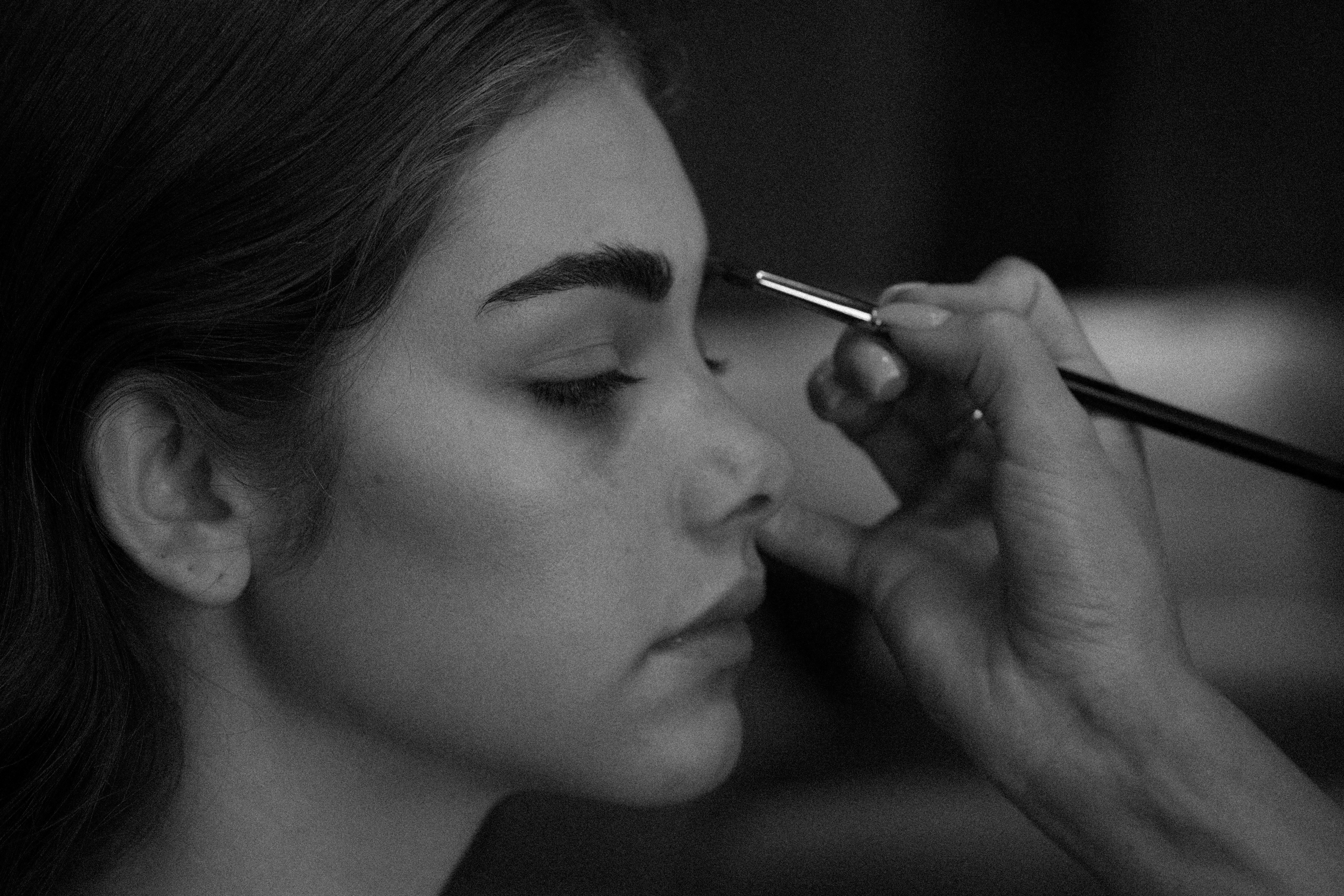 Cara applying Seint makeup on a model