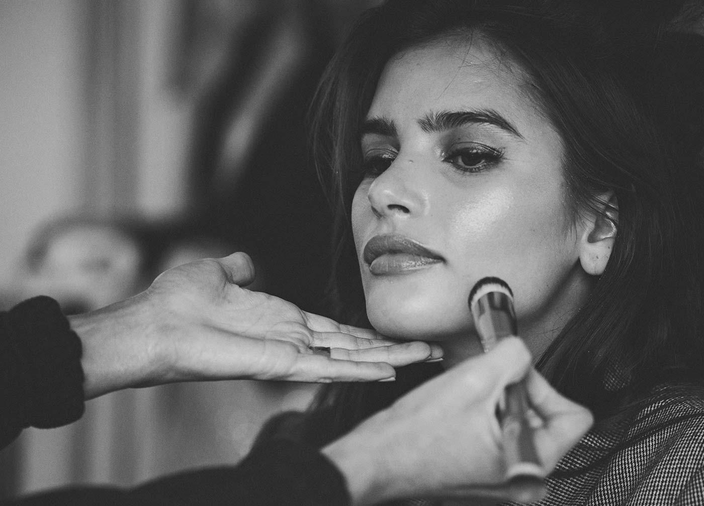 Cara applying Seint makeup on a model