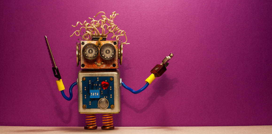 Small handmade robot standing against a purple wall.