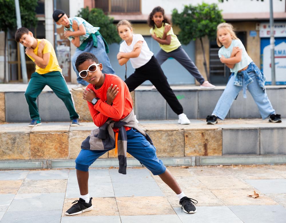 Little boy hip hop dancer exercising with friends at open air dance class